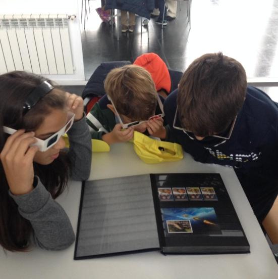 """Algunos de los jóvenes que participaron en """"el taller de filatelia"""", mirando divertidos, con las gafas especiales, sellos en 3D"""